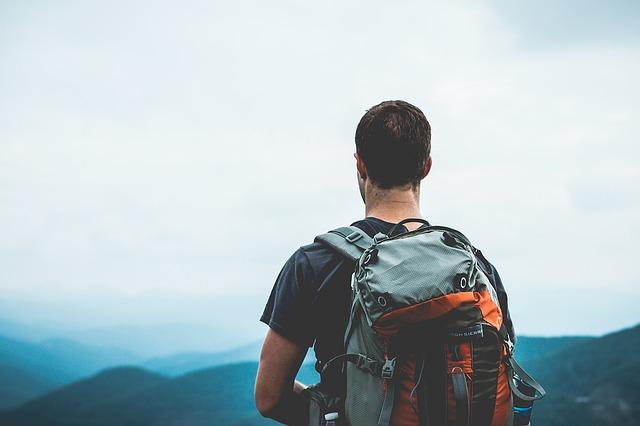 muž v horách s batohem na zádech