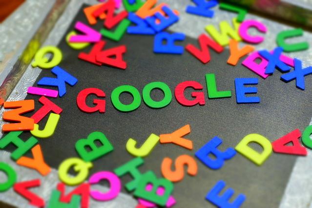 název firmy Google sestavený z barevných písmen na zemi